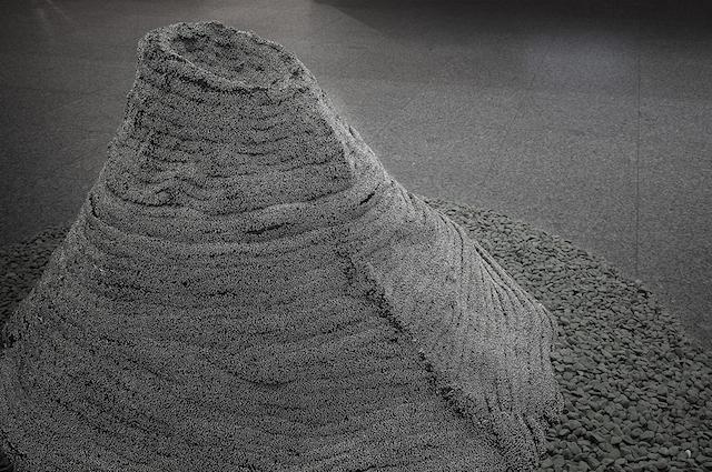 ©土田泰子《掴〜頂きたくて〜》2012年 安全ピン・墓石
